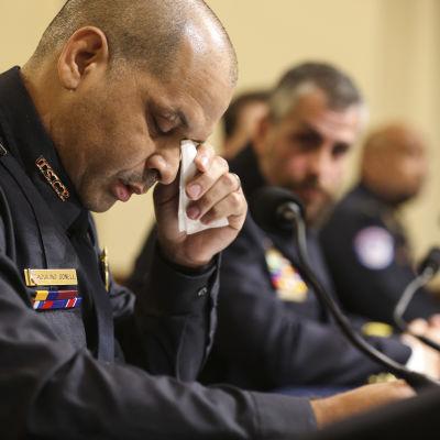 Poliser på rad sitter vid ett bord. En av dem gråter medan de vittnar om händelserna i kongressen 6 januari 2021.