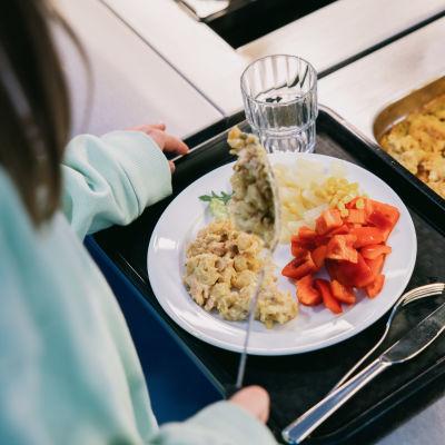 Koululainen ottaa itselleen ruokaa.