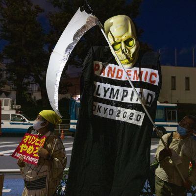Mielenosoittaja Tokion olympiastadionin ulkopuolella.
