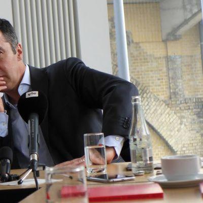 Saksan vihreiden puheenjohtaja Cem Özdemir istuu pöydässä kolmen mikrofonin takana.