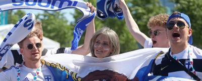Tre finska fotbollsfans med halsdukar med texten Suomi. I mitten ses ett ryskt fotbollsfan med en rysk flagga i handen.