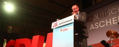 Friedrich Merz talar på en scen. På scenen står det CDU med stora röda bokstäver.