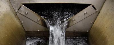 Vatten rinner ner från en metallucka.