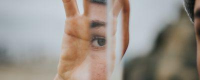 En person håller en liten spegel så att man ser endast en ena ögat speglas i spegeln.