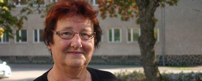 Maj-Britt Malmén, en kvinna med rött, kort hår och glasögon står utomhus med ett grönt träd och en brunaktig byggnad i bakgrunden.