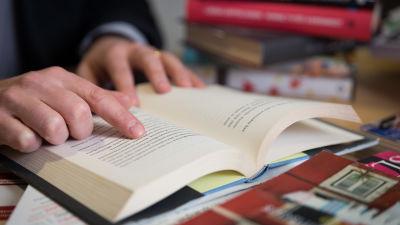 Lähikuva kirjasta ja kädestä.