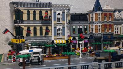 En bit av en legostad med folk och bilar i förgrunden