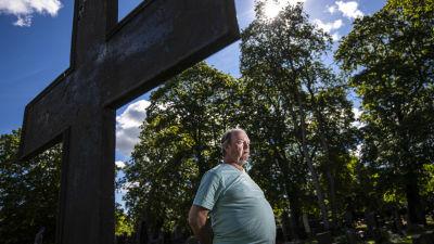 En man står med händerna bakom ryggen framför ett stort kors på en kyrkogård.