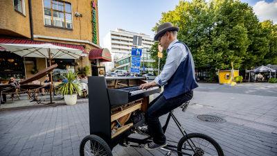 En man med hatt spelar på ett portabelt piano.