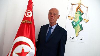 Bild på man som står vid tunisiens flagga.