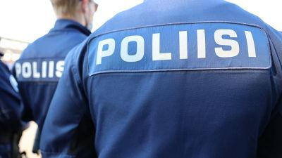 Ryggarna på poliser där det på finska står poliisi.