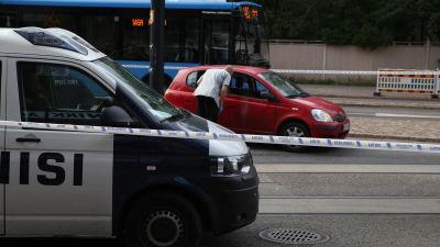 Polisen har spärrat av området där den röda bilen, som varit med om skottlossningen, står.
