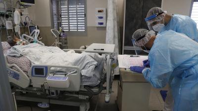 Coronapatient som ligger i en sjukhussäng och två läkare eller sjukvårdare som står framför sängen och antecknar något på ett papper.