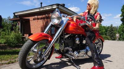 En man i röd läderväst sitter på en röd motorcykel och ler.