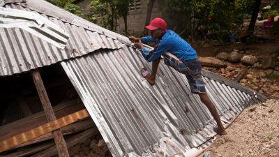 En man bygger ett skydd mot regnet.