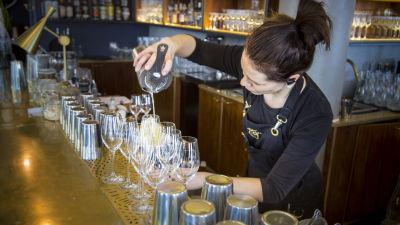 Tarjoilija kaataa drinkkiä lasiin.