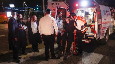 Två personer hjälper en tredje vid en ambulans till höger. Till vänster fyra personer till.