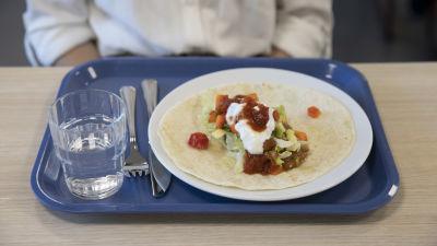 En tallrik med en tortilla med vegetarisk sås på. Under den en skolmatsalsbricka av blå plast.