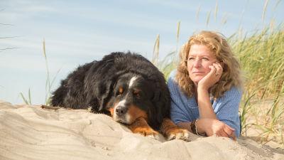 Medelålders kvinna ligger i sanden bredvid stor svart hund