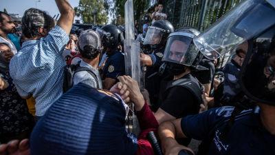 Protester utanför parlamentsbyggnaden i Tunis. Polisen sammardrabbar med demonstranter.