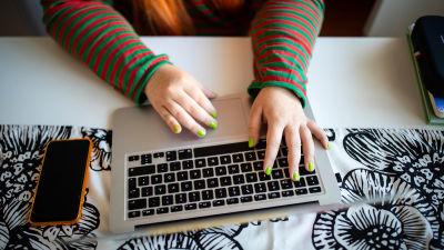 Studerandes händer som skriver på en bärbar dator.