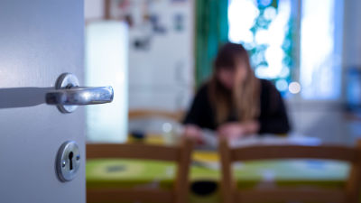 En anonym kvinna sitter i ett kök. Bilden är suddig så att man inte kan urskilja vem hon är.