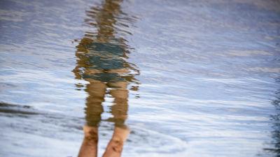 En kvinnas spegelbild syns i vågigt vatten