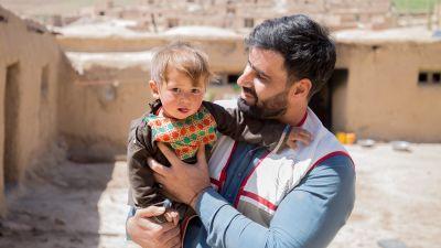 en afghansk pappa med ett barn i famnen