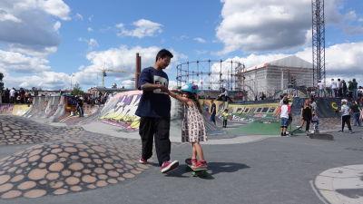 Pappa som drar sin fem-åriga dotter på en skejtboard i Söderviks skejtpark