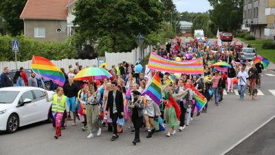 En färgglad prideparad med många människor går på en gata.