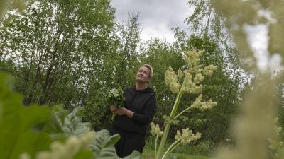 Koronapandemian takia työttömäksi joutunut Johanna Virta, seisoo puutarhassaan raparperinippu sylissään ja katsoo taivaalle.