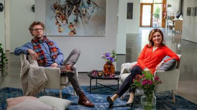 Antti Reini och programledaren Ira Hammermann sitter i varsin vit fåtölj i ett konstgalleri.