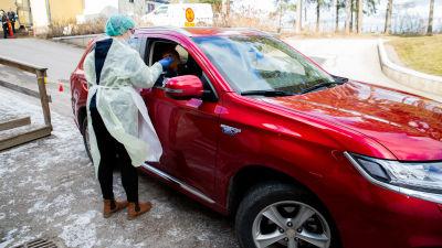 En sjukvårdare i skyddsutrustning ta ett coronavirustest på en person som sitter i en röd bil.