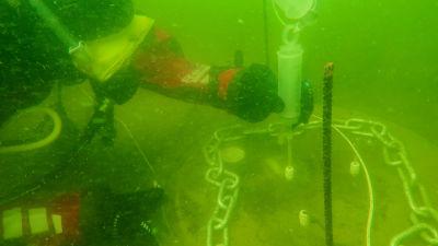 Bild av dykare som tar vattenprov under havsytan.