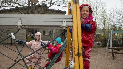 Dagisbarn klättrar i lekställningar på en dagisgård.