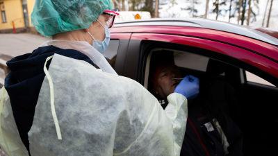 En skötare i skyddskläder sticker in en provtagningssticka i näsan på en man som sitter i en bil.
