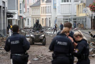 Polis patrullerar i Tyskland under översvämningarna. En person åker fyrhjuling i bakgrunden.