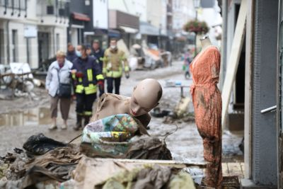 Räddningsmannskap hjälper en äldre kvinna att gå längs med en gata som kantas av små affärer. I förgrunden ligger en skyltdocka.
