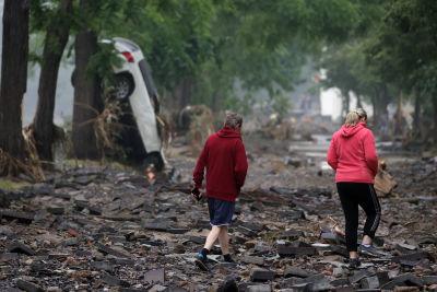 Två kvinnor går tittar på förödelsen efter översvämningarna och en bil som står vertikalt lutad mot ett träd med motorhuven mot marken.