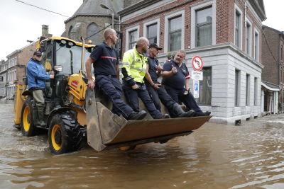 Räddningsinsatsen är i full gång i Belgien. Här åker fyra män i en grävskopa för att komma fram på de vattentäckta vägarna.Räddningspersonalen tar sig fram på gatorna med hjälp av båtar.