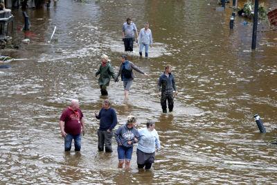 Människor vadar i brunt vatten på gator i Belgien