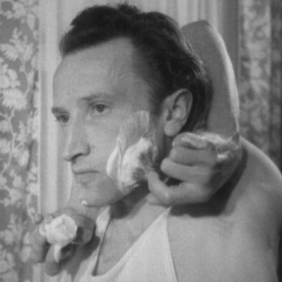 Mies ajaa partaa kädet solmussa