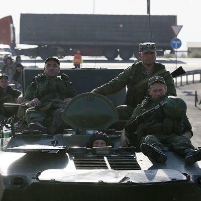sotilaat istuvat sotilasajoneuvojen päällä