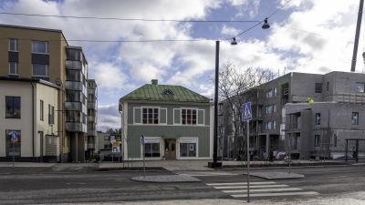 Vanha, vihreä puutalo uudisrakennusten välissä Sipoon Nikkilässä.