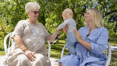 Två kvinnor sitter på stolar i en trädgård. Den ena håller upp ett barn och den andra håller i barnets hand.