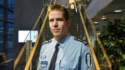 Man iklädd polisunform tittar in i kameran med neutralt ansikte. En aula med trappa i bakgrunden.