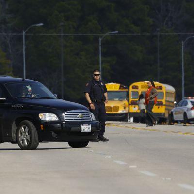 Poliiseja, poliisiautoja ja koulubusseja tiellä