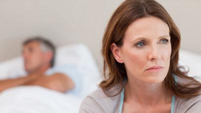 Ledsen kvinna sitter på en säng med en man i bakgrunden.