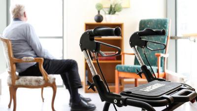 Äldre man sitter på en stol och tittar bort. I förgrunden ser man handtagen till en rollator.