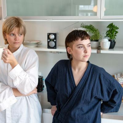 Kaksi naista valkoisen hyllyn edessä, taustalla radio